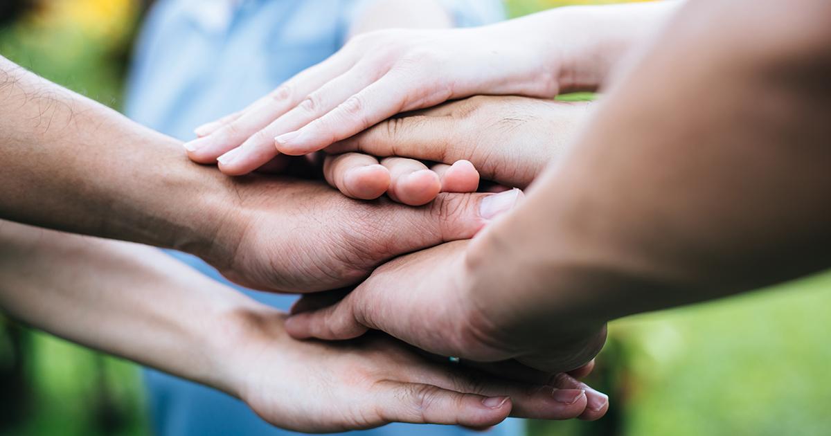 mains les unes sur les autres symbole de solidarité dans une association
